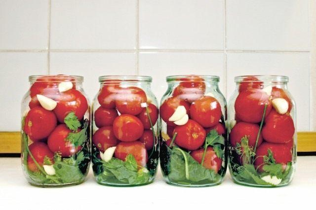 Выложите дно зеленью, плотно уложите томаты
