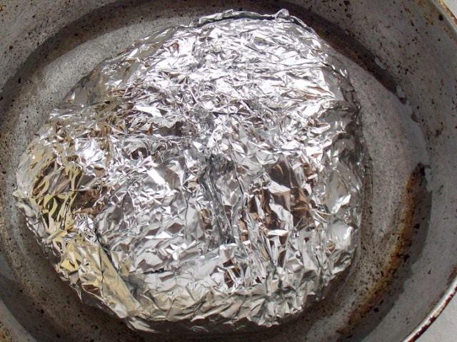 Положите завёрнутое в фольгу мясо в чугунную сковороду