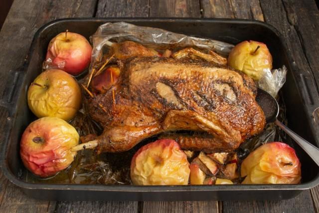 Достаём утку из духовки, разрезаем рукав, вокруг раскладываем целые яблоки и ставим утку под гриль на 15-20 минут
