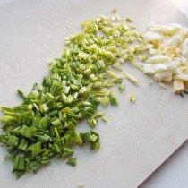 Нарежте отваренные яйца и черемшу