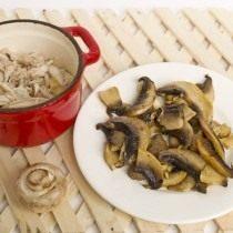 Выкладываем мясо в кокотницу, сверху выкладываем обжаренные грибы