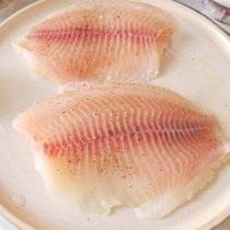 Обсушите филе морского окуня, приправьте специями и солью