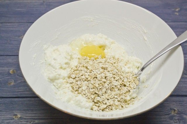 Добавляем в миску сырой желток, щепотку соли и овсяные хлопья