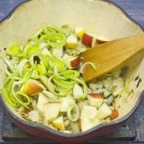 Добавляем лук порей и кусочки яблок в жаровню, готовим 5 минут
