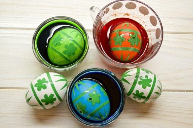 Кладём яйца в чашки с цветным раствором