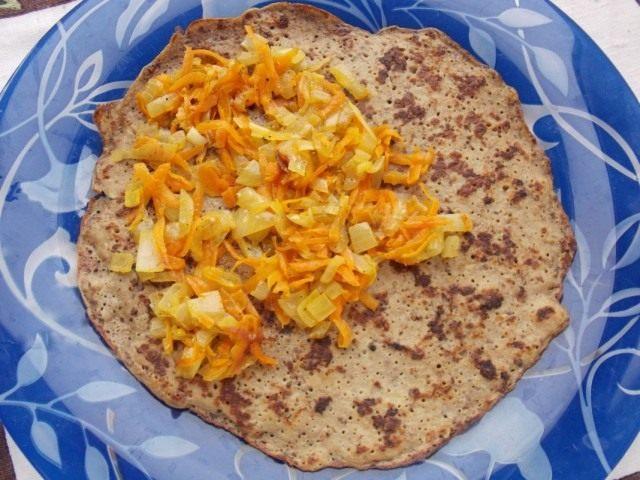 Выкладываем первым слоем начинку из обжаренных лука и моркови