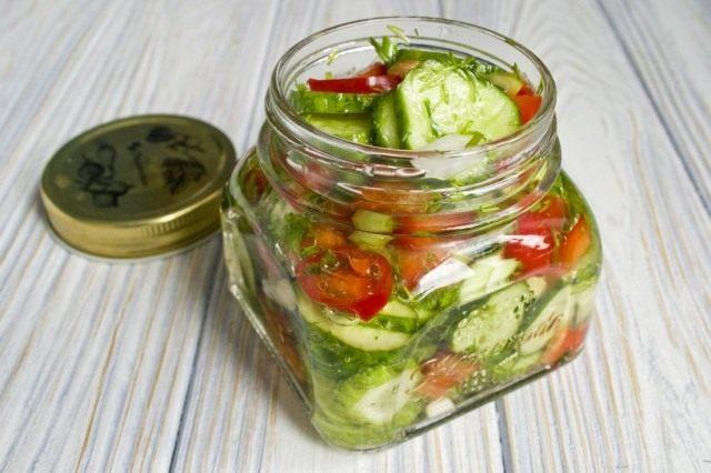 Раскладываем салат из огурцов с болгарским перцем по банкам и стерилизуем