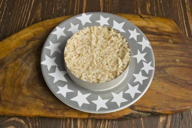 На тарелку выкладываем порцию отваренного бурого риса