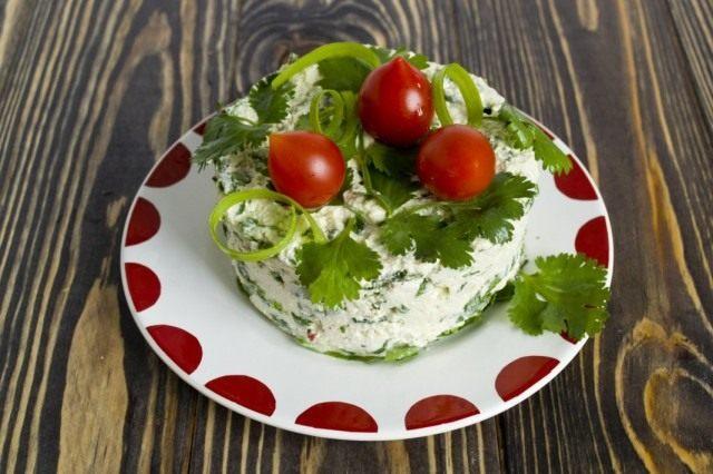Выкладываем на тарелку салат с творогом, шпинатом и кинзой. Украшаем зеленью и помидорами