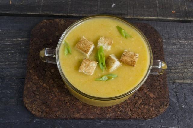 Наливаем куриный крем-суп в тарелку и посыпаем гренками и зеленью