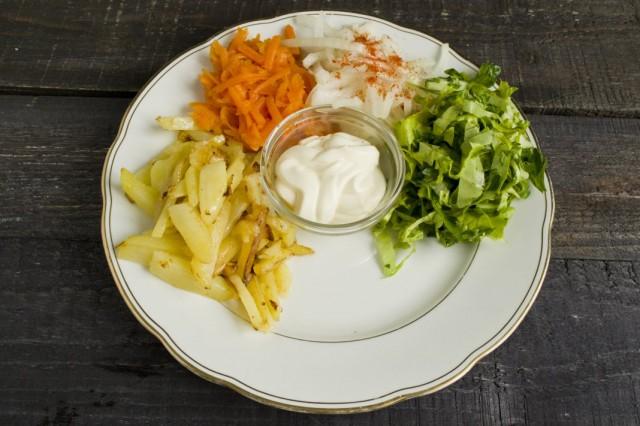 Выкладываем на тарелку нарезанные салат и зелень