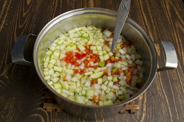 В кастрюле обжариваем нарезанные овощи, затем заливаем отваром от нута