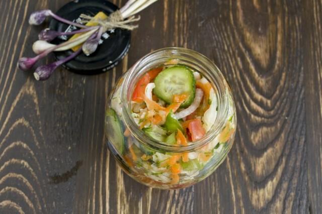 Перекладываем капустный салат с огурцами и помидорами в стерилизованные банки и закручиваем