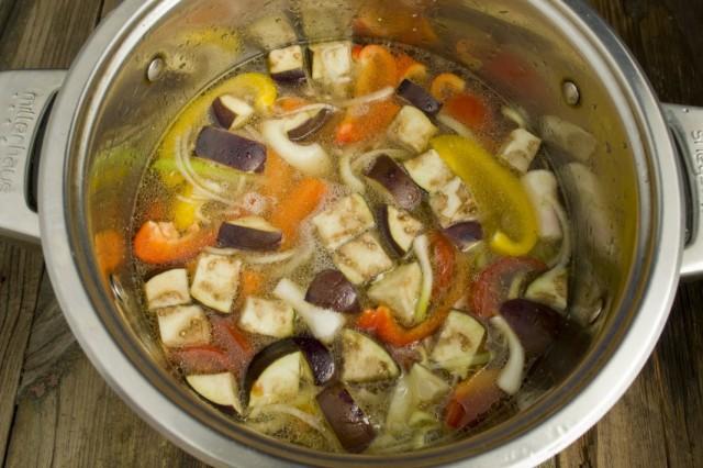 Складываем овощи в кастрюлю, добавляем баранину и заливаем бульоном