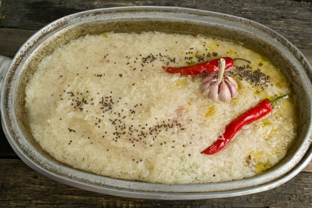 Выкладываем острый перец, чеснок, пряности и заливаем холодной водой