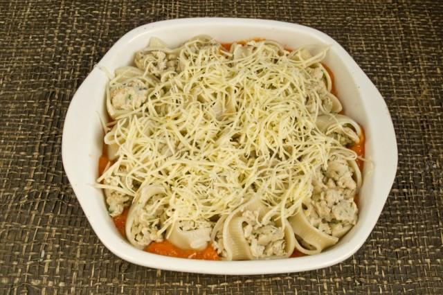 Посыпаем фаршированные макароны в томатном соусе натёртым сыром
