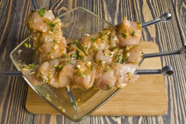 Нанизываем кусочки куриного филе на шампуры