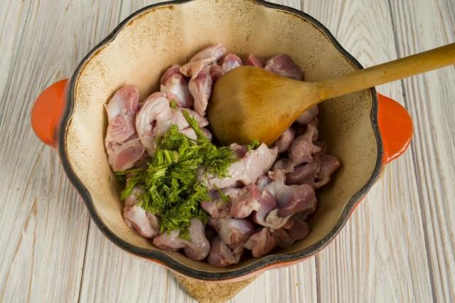 В жаровню выкладываем куриные желудки, рубленные чеснок и зелень