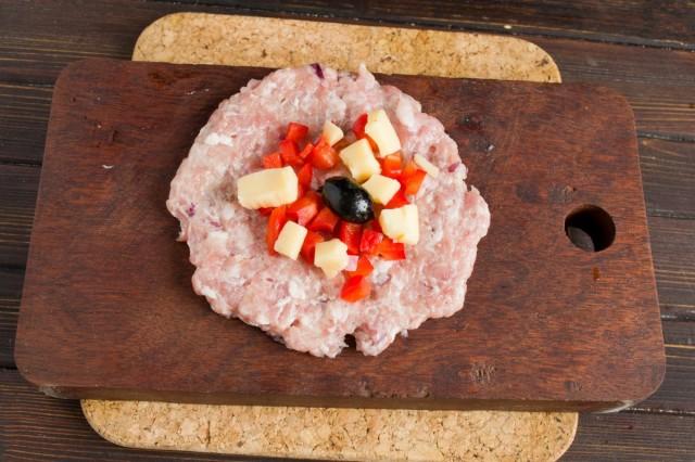 Добавляем к нарезанному перцу оливку без косточки и нарезанный сыр