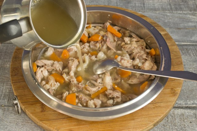 В разогретом бульоне разводим желатин и заливаем им мясо. Добавляем оставшийся бульон