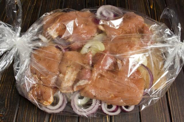 В пакет для запекания укладываем нарезанный лук, сверху кладём маринованное мясо