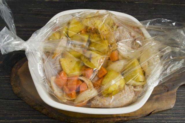 Кладём упакованную курицу с овощами в огнеупорную форму для запекания