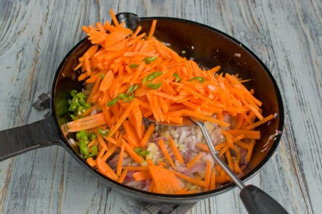 Добавляем в сковороду нашинкованную морковь и нарезанный острый зелёный перец