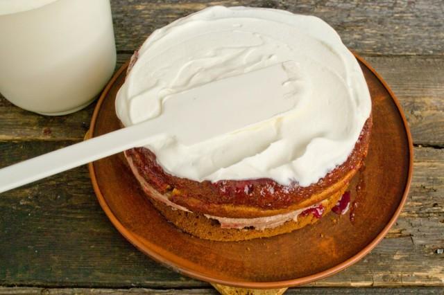 Обмазываем тортик сверху и по бокам толстым слоем взбитых сливок