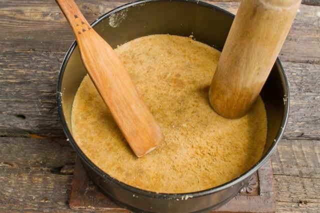 Смешиваем растопленное сливочное масло с песочной крошкой и выкладываем в форму