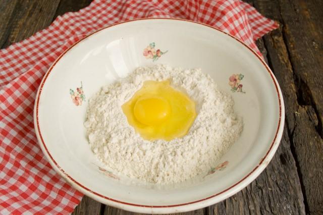 Насыпаем в миску пшеничную муку высшего сорта, в ямку разбиваем крупное куриное яйцо