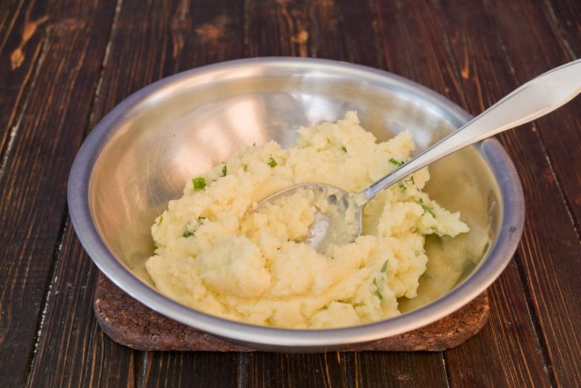 Разминаем отваренный картофель, добавляем сливочное масло и зелёный лук
