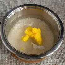 Насыпаем рис в кастрюлю, добавляем холодную воду и топленое масло