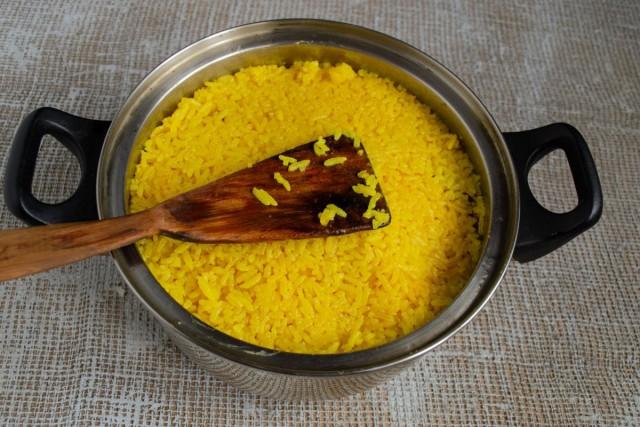 Укрываем овощи и мясо слоем горячего риса, палочкой протыкаем в нескольких местах, вливаем бульон