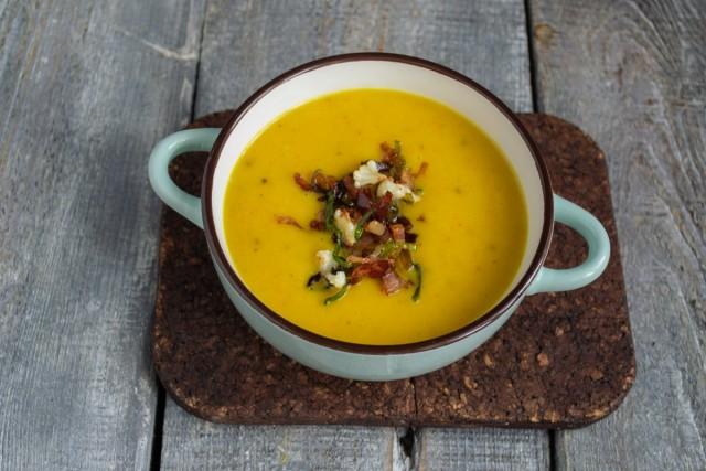 Подаём рыжий крем-суп из цветной капусты горячим, с хрустящим беконом и поджаренными гренками