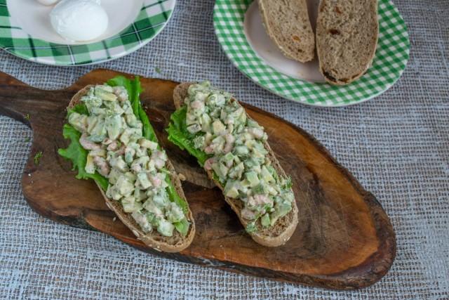 Кладём на хлеб листики салата, на них выкладываем салат из креветок с авокадо