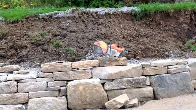Сухие подпорные стенки начинают возводить с самых крупных камней, укладывая на них камни поменьше