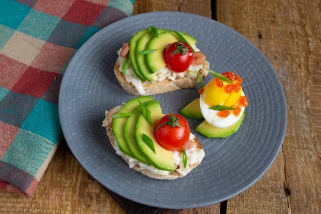 Украшаем тосты с авокадо помидорами черри и зелёным луком. Подаём с варёным яйцом и красной икрой