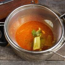Процеживаем куриный бульон и вливаем в кастрюлю с овощами
