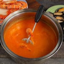 В кипящий суп бросаем морепродукты. После того как он снова закипит, варим ещё 2-3 минуты
