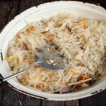 Закрываем все ингредиенты в жаровне слоем подготовленной квашеной капусты