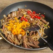 Нарезаем сладкий болгарский перец и чили, прогреваем с мясом на среднем огне