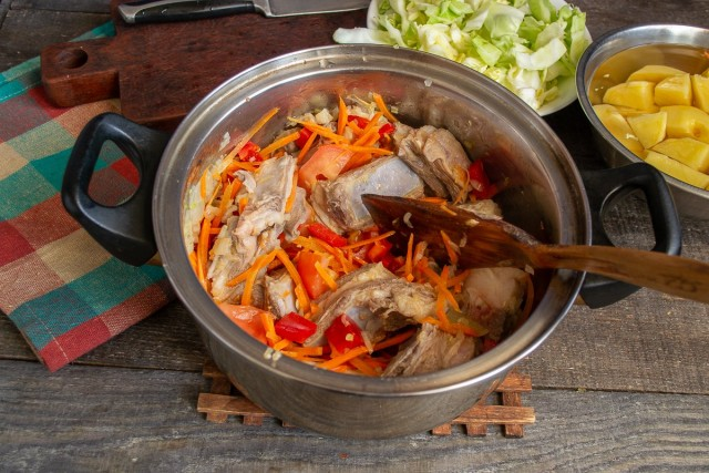 Тушим овощи и добавляем рёбрышки. На сильном огне быстро обжариваем мясо с овощами