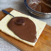 Выкладываем на первый корж половину шоколадного крема