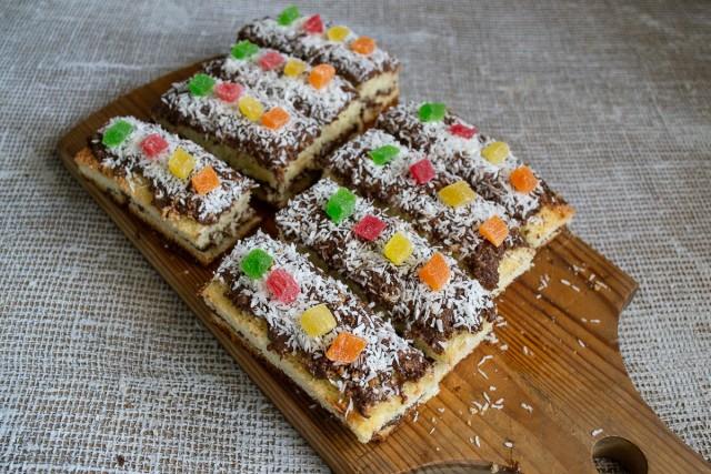 Посыпаем бисквит кокосовой стружкой, нарезаем одинаковые пирожные и украшаем цукатами
