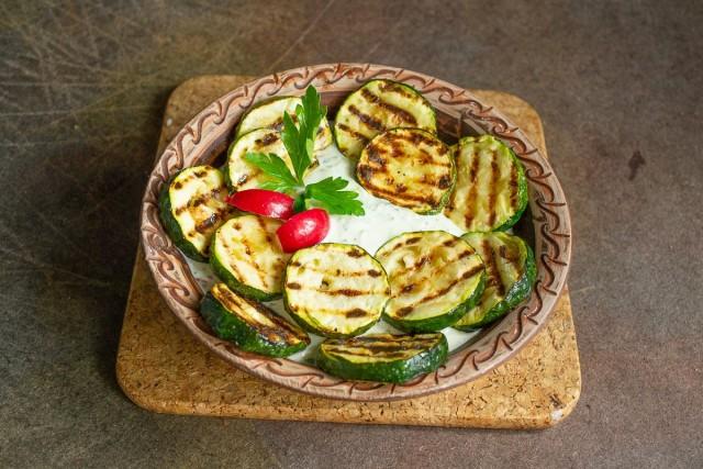 Подаём кабачки горячими прямо с гриля, добавляем соус и украшаем зеленью