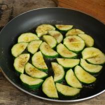 В растопленное масло выкладываем кабачки, жарим их с одной стороны 5 минут