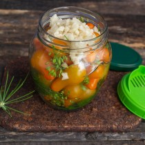 Сливаем воду с овощей, кладём на черри нарезанный чеснок