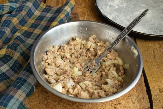 Для начинки к рыбе добавляем лук, всё вместе разминаем вилкой, перемешиваем