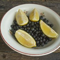 Разрезаем ошпаренный лимон, извлекаем косточки над ёмкостью с ягодами