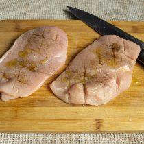 Солим и перчим курицу, втираем приправы, поливаем маслом